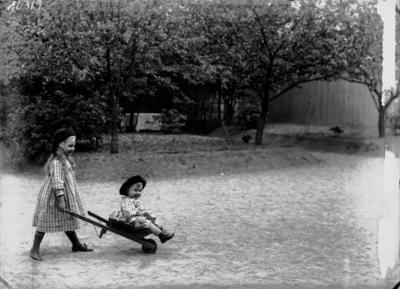 Två småflickor, Märta och Margit Lindskog. Märta skjutsar sin lillla syster Margit i skottkärra.