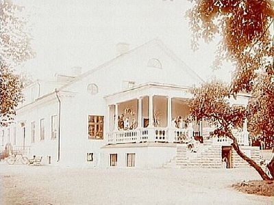 Sörby herrgård, envånings herrgårdsbyggnad med frontespis, stor öppen veranda på ena gaveln. 7 personer på verandan. Baron Gustaf Djurklou