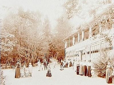Restaurangen, tvåvåningsbostadshus i trä med glasad veranda och öppen balkong. Brunnsgäster.  Fru Elin Elander.