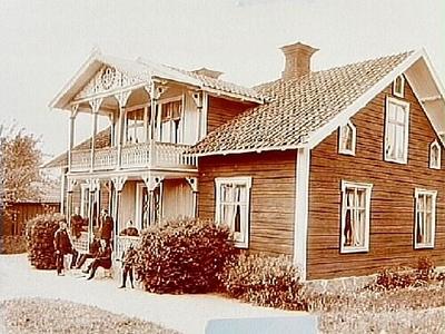 En och en halvplans bostadshus med veranda och balkong, snickarglädje. 7 personer på trappan till verandan. Johansson.