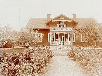 Envånings bostadshus med inredd vind, takhuv, balkong och veranda i snickarglädje. Trädgård med en staty på rundeln. 5 personer och en hund på verandan. Postmästare C.G. Kaxell