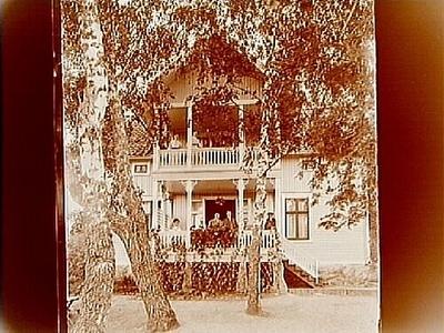 En och en halvvånings bostadshus, med veranda och balkong. 2 personer på balkongen, 7 personer på verandan. Fröken Maria Jonsson