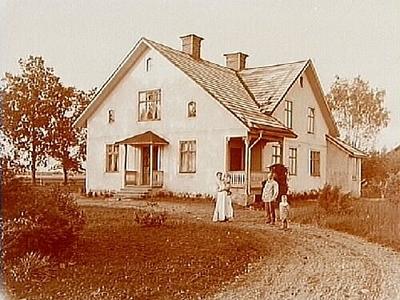 En och en halvvånings bostadshus med veranda och förstubro. Familj 4 personer framför huset. Karl Andersson