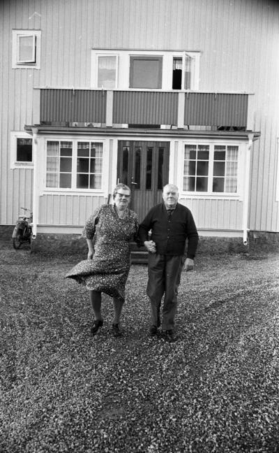 Förlovade Gamlingar 22 nov 1967  En kvinna och en man kommer gående och håller varandra i handen. Bakom dem ser man huset och en moped.
