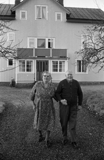 Förlovade Gamlingar 22 nov 1967  En kvinna och en man kommer gående hand i hand på grusgången framför huset.