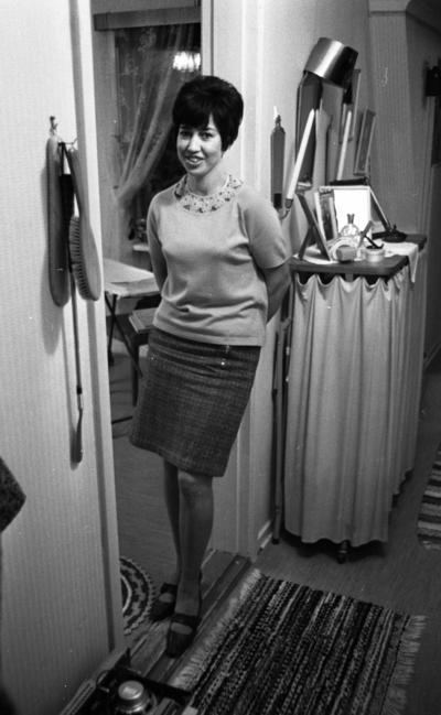 Betania villan 12 oktober 1966  En kvinna står i hallen i sin bostad. På vägggen hänger  det en borste och ett skohorn. Bakom henne syns ett skåp med ett draperi.