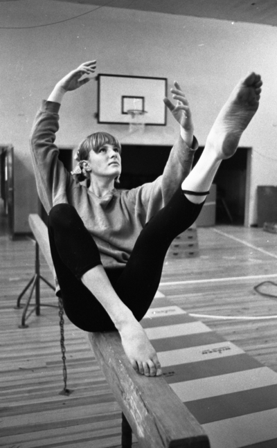 Gymnastik, 7 november 1966  Gymnast Ingrid Hansson gör rörelser på en bom. Hon har en tröja och gymnastikbyxor på sig.  På väggen sitter det en basketkorg.