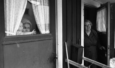 Gyttorp 2 23 februari 1967  En kvinna med glasögon är klädd i rock och tröja står i dörren och tittar ut. Dörren bredvid står en kvinna med ett barn.
