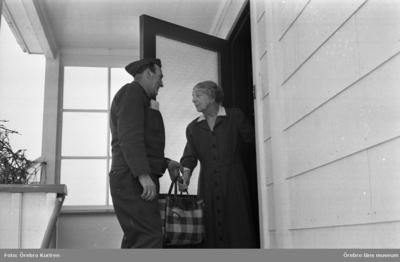 Bryggaren 1 - 1 februari 1969  En man från Pripps Bryggeri levererar drycker till en kvinna i klänning på en veranda. Hon får dryckerna i en rutig väska.