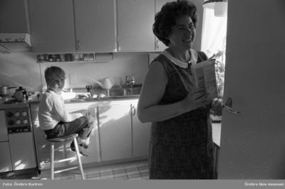 Vår mor 29 maj 1969  En kvinna står i ett kök och håller ett mjölkpaket i handen. På en pall vid diskbänken sitter en pojke. Han har några leksaksbilar på diskbänken.