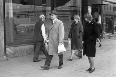 Folk går på systemet, 11 maj 1965.  Bilden tagen på Drottninggatan, del av apoteket Svanens skyltfönster syns.