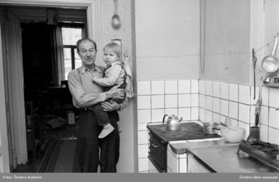 Gamla söder 27 januari 1970  En man i rutig skjorta står i köket och håller ett barn i famnen.