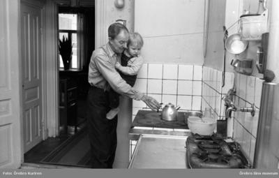 Gamla söder 27 januari 1970  En man i rutig skjorta står vid spisen och kokar kaffe. Han håller ett barn i famnen.
