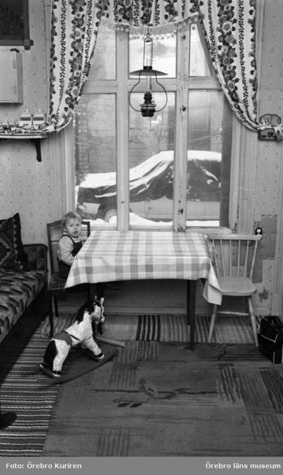 Gamla söder 27 januari 1970  Det sitter en pojke vid köksbordet och över bordet hänger det en fotogenlampa. På golvet står en gunghäst.