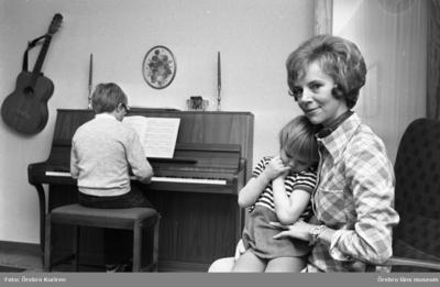 En kvinnas dagbok, Hemmafru Göhle 7 december 1970  En pojke sitter och spelar på ett piano. Bakom honom sitter en kvinna i rutig klänning med en flicka i knäet. På väggen hänger det en gitarr.