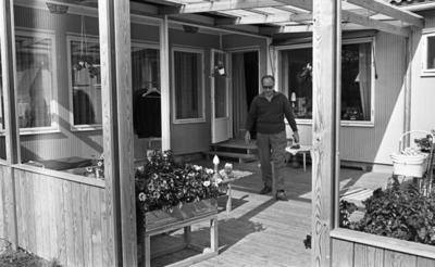 Hasselfors bruk 19 augusti 1965  En liten flickbaby med hätta på huvudet ligger på mage på en filt på en veranda vid Hasselfors bruk. En äldre man går från henne i riktning mot kameran. En kvinna i mörk blus samt förkläde står inne i huset i bakgrunden av bilden och tittar ut genom fönstret. Ute på verandan står två dockvagnar, litet bord med barnstol till samt leksaker. Från taket till vänster hänger en ställning med två herrkavajer upphängda på galgar. Två amplar hänger även från taket. I förgrunden står en blomlåda med blommor i.