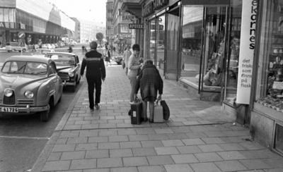 Gentlemen finns de, 15 september 1965  Bildserie: en kvinnlig journalist med flera resväskor testar hjälpsamheten hos medmänniskorna. Här i samtal med en ung flicka samtidiigt som hon visar hur tunga väskorna är. Flickan har uppsatt hår och slacks. En yngling med islandströja passerar. Saaben har delad framruta.