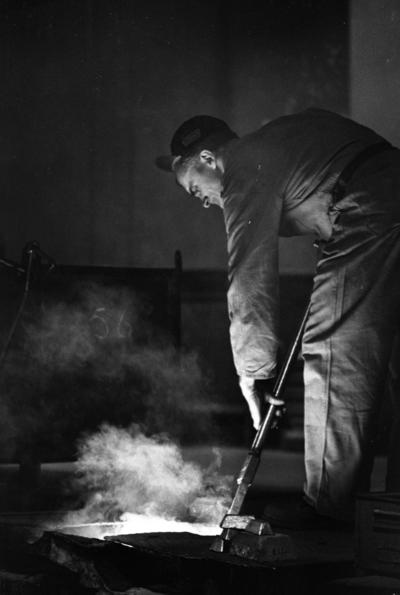 Johnson metall, 21 januari 1966  På bilden syns en metallarbetare iklädd arbetsoverall, livrem och keps  i sitt arbete med metall vid ugnen på