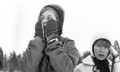 Hästnäs, 20 januari 1966  På bilden syns det ansiktena av två flickor. I bildens förgrund centralt syns det en flicka som är klädd i vinterkläder. Flickan har vantar på sina händer som hon håller vid sina kinder, handflatorna vända mot kinder. Den andra flickan som syns åt höger i förgrunden har en ljus stickat vintermössa på sitt huvud.
