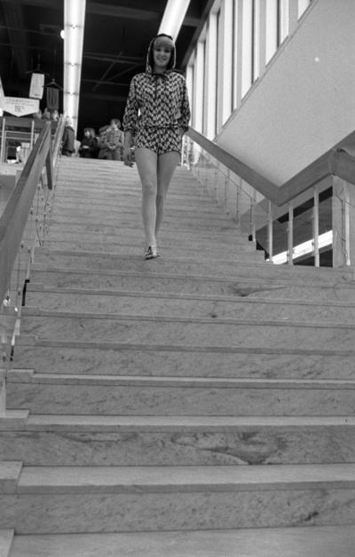 Baddräkter 12 maj 1966  En fotomodell iklädd rutig munkjacka och shorts samt med sandaler på fötterna går nedför en trappa. På toppen av trappan i bakgrunden syns publik.                                                                                                                 or. Han går nedför en kort trappa utomhus.