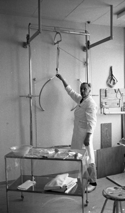 Ortopeden 28 februari 1966  En man i vit rock vid namn Holmgren och träskor står vid redskap som används för utprovning av proteser åt handikappade. En stor metallställning finns bakom honom. Framför honom står ett bord med en vattenskål, handdukar samt diverse verktyg. Vid sidan om bordet står en pall. I bakgrunden på väggen till höger i bild skymtar olika ortopedverktyg.