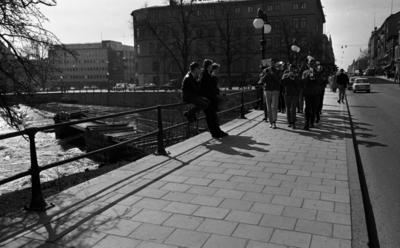 Våren 29 april 1966  En mässingsorkester går Drottninggatan fram och spelar. Två unga män sitter och en står vid broräcket till vänster på bilden. I bakgrunden syns andra personer, byggnader samt bilar.