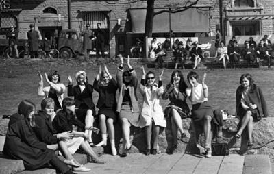 Våren 29 april 1966  Elva glada flickor sitter i en park i centrala Örebro. I bakgrunden till höger. syns äldre personer som sitter på parkbänkar. En kvinna med en barnvagn syns även. Till vänster står några män framför en lastbil. Ett barn med en cykel står också där.