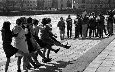 Våren 29 april 1966  Åtta stycken unga flickor står i en lång rad och dansar till en mässingsorkester som spelar i Centralparken i Örebro.