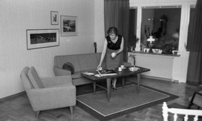 Byggspecial Oxhagen 11 februari 1966  I ett vardagsrum i en lägenhet i Oxhagen står en kvinna klädd i svart linne, grå kjol och sandaler och dukar ett bord. I rummet finns en soffa, en fåtölj och en matta under bordet.
