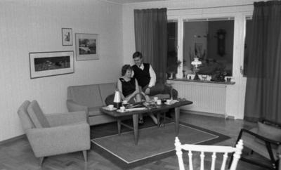 Byggspecial Oxhagen 11 februari 1966  I ett vardagsrum i Oxhagen sitter en man och en kvinna. Hon är klädd i svart linne, grå kjol och har sandaler på fötterna. Kvinnan sitter i soffan och mannen sitter uppe på soffans ena armstöd. Han är klädd i vit skjorta, svart väst, grå byxor och svarta skor. En fåtölj samt en stol finns också med på bilden. I bakgrunden finns stora fönster samt gardiner. På väggarna hänger tre tavlor.
