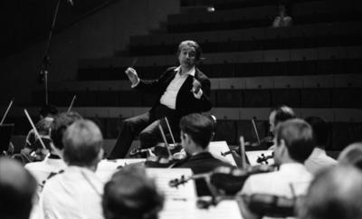 Cellibedache 13 juni 1966  En dirigent klädd i vit skjorta, svart kavaj och svarta byxor viftar med taktpinnen framför en orkester. Framför honom sitter ett antal personer i orkestern som spelar fiol. I bakgrunden syns publikens sittplatser.