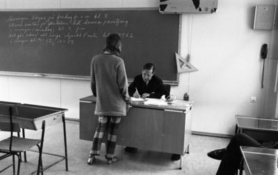 Beg. bilar, Ferieskola, Bodenkille slog rekord 14 juli 1966  En lärare klädd i mörk kostym, mörk slips samt vit skjorta sitter vid sin kateder och skriver på ett papper. Framför honom står en ung kvinna klädd i tröja, rutiga byxor samt med ett par sandaler på fötterna.