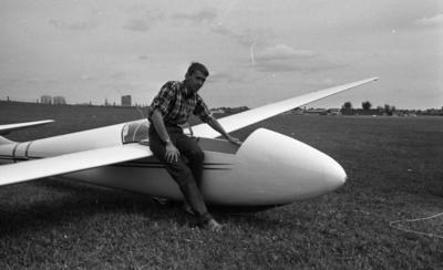 Beg. bilar, Ferieskola, Bodenkille slog rekord 14 juli 1966  En ung man klädd i rutig skjorta, långbyxor samt sandaler sitter på vingen till ett litet flygplan. Planet ligger på marken.