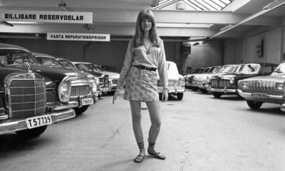 Kort- kort på jobb 2 augusti 1966  En ung kvinna med långt hår, långärmad tröja, kort kjol, halsband runt halsen och med sandaler på fötterna står inne i en lokal fylld med bilar. Två skyltar hänger i taket. På den ena står det: