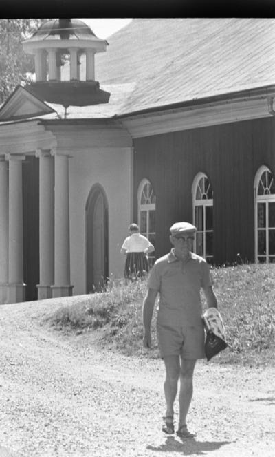 Loka brunn 2 22 juli 1966  En äldre herre klädd i keps, kortärmad tröja, shorts och sandaler promenerar på en väg i kurorten Loka brunn. Han bär glasögon samt något i sin vänstra hand. En kvinna samt en byggnad syns i bakgrunden.