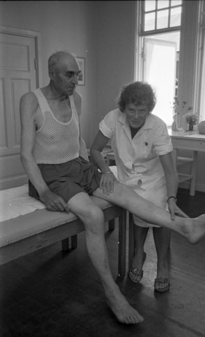Loka brunn 22 juli 1966  En äldre herre klädd i vit nätundertröja samt mörka shorts sitter på en brits och sträcker ut vänstra benet. En kvinna klädd i vita arbetsklädsel håller i hans ben. Ett vitt bord syns i bakgrunden.