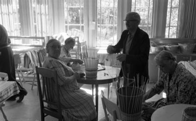 Loka brunn 22 juli 1966  Tre äldre damer och en herre är i full färd med att tillverka korgar inne i ett rum på kurorten Loka brunn. Damerna sitter på stolar vid runda bord. Herrn står upp. Stora fönster syns i bakgrunden.