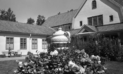 Loka brunn 22 juli 1966  Bild på en byggnad i kurorten Loka brunn. I förgrunden syns en stor kruka som står på gräsmattan samt blommor. En ung kvinna i kort klänning promenerar längs med husväggen i bakgrunden.
