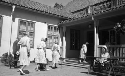 Loka brunn 22 juli 1966  Fyra äldre damer klädda i klänningar och två äldre herrar klädda i kostymer är på väg mot entrén på en av byggnaderna i kurorten Loka brunn. Till höger sitter en yngre kvinna vid ett bord. I dörröppningen till entrén står en annan kvinna.