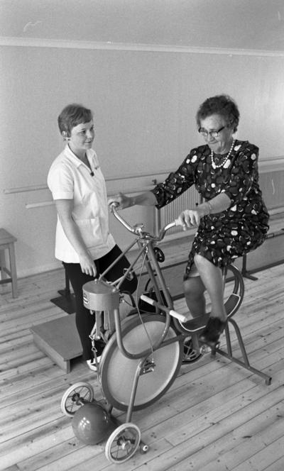 Loka brunn 22 juli 1966  En äldre dam i knäkort klänning cyklar på en motionscykel under överinseende av en arbetsklädd tränare på kurorten Loka brunn.
