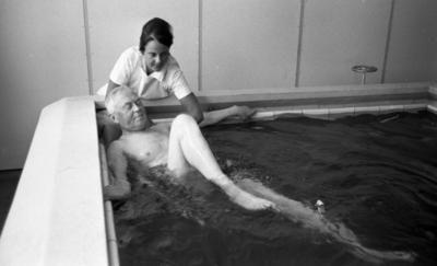 Loka brunn 22 juli 1966  En äldre man badar i bassängen och sparkar med benen på kurorten Loka brunn. Invid honom vid bassängkanten står en kvinna i vit arbetsrock och övervakar hans träning.