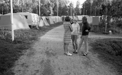 Missionsläger 10 augusti 1967  Tre ungdomar står och samtalar på en väg på ett missionsläger. I bakgrunden syns en husvagn samt en massa tält. Den unga flickan till vänster bär en kort klänning samt träskor, flickan i mitten är klädd i tröja, byxor och sandaler medan flickan till höger är klädd i tröja, byxor, sandaler och strumpor. Ytterligare personer syns i bakgrunden.