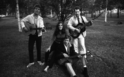 Modellbåts-SM, Mosås 21 augusti 1967  En musikgrupp bestående av en kvinna och tre män. Två av männen står upp med gitarrer i sina händer. I mitten sitter kvinnan klädd i tröja och byxor invid den tredje mannen som också har en gitarr i sina händer. Tre av medlemmarna har sandaler på fötterna.