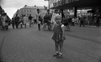 Marknadsafton 16 juni 1967  En liten flicka klädd i en liten klänning, hätta på huvudet, underbyxor, strumpor och sandaler står på gatan i centrala staden Örebro under en marknadsafton. Det är fullt av folk på gatan, däribland mammor med barnvagnar och man ser affärer och byggnader runtomkring.