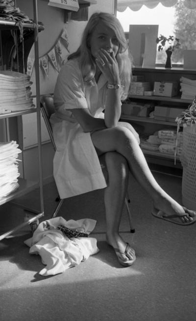 Orubricerad 5 augusti 1967 Travkusk Bengt Nilsson  En ung flicka i vit arbetsrock och med flip-flops på fötterna sitter på en stol i ett rum på Gustavsviksbadet. Hyllor står utplacerade runt omkring henne fyllda med handdukar m.m.