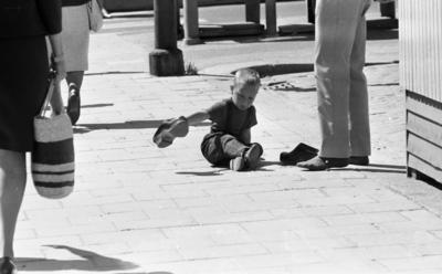 Kvar i stan 26 juli 1967  Ett antal människor befinner sig i centrala stan i Örebro. Närbild på en liten pojke i treårsåldern klädd i svart T-shirt, svarta hängselbyxor, mörka strumpor och mörka sandaler som sitter på gatan och håller i en vuxen mans träsko. Den andra träskon står bredvid honom på marken. En barfota man i vita byxor står bredvid honom. Två kvinnor i klänningar passerar dem.