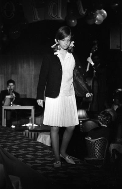 Korsettuppvisning 26 april 1965  Yngre kvinnlig modell i kjol, skjorta & jacka med rosetter i håret. Firma Härold, Hagenfeldts personalvisning på Frimis.