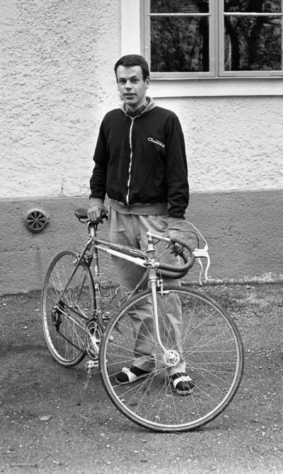 Palle Munther 18 maj 1967  En ung man klädd i svart sportjacka med ljusa kanter, rutig skjorta, grå byxor, svarta strumpor och vita sandaler står och håller i en sportcykel.