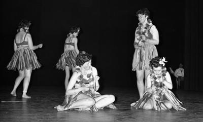 Göthman, Handikappfest,18 maj 1967  Fem kvinnor befinner sig på scenen under en revyföreställning på teatern. Alla är klädda i bikiniöverdelar, bastkjolar och har blomsterkransar runt halsarna. Två av dem sitter i förgrunden och spelar på trianglar. De tre andra står upp och dansar omkring och en av dessa kvinnor spelar också triangel.