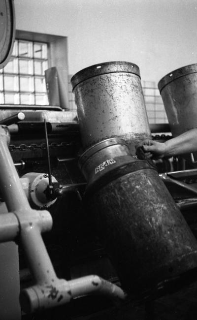 Mjölkrep 9 februari 1967  En mjölkkanna av metall inne i en fabriksbyggnad i en livsmedelsindustri. En maskin syns även på bilden.